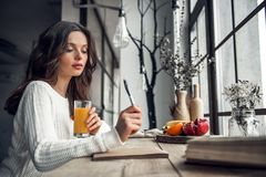 Girl at home. Beautiful young girl in casual clothes is writing in the notepad and holding a glass of juice while sitting at the wooden table at home Stock Photo
