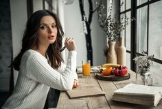 Girl at home. Beautiful young girl in casual clothes is writing in the notepad and looking at camera while sitting at the wooden table at home Royalty Free Stock Photography