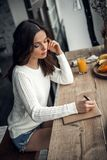 Girl at home. Beautiful young girl in casual clothes is writing in the notepad while sitting at the wooden table at home Royalty Free Stock Image
