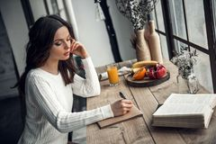 Girl at home. Beautiful young girl in casual clothes is writing in the notepad while sitting at the wooden table at home Stock Image