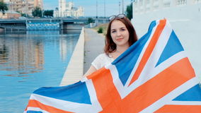 Beautiful young girl in casual style smiling with Great Britain flag in her hands. Ginger hair, water on background stock video