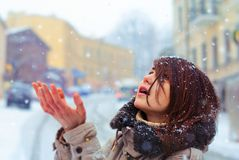 Beautiful young girl is catching snow in the winter city Stock Image