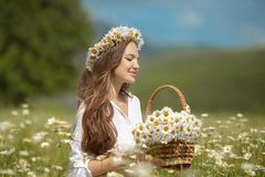 Beautiful young girl in chamomile field. Carefree happy brunette. Woman with healthy wavy hair having fun outdoor in nature. Daydreaming royalty free stock images
