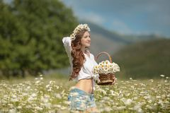 Beautiful young girl in chamomile field. Carefree happy brunette. Woman with healthy wavy hair having fun outdoor in nature. Daydreaming royalty free stock photos