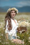 Beautiful young girl in chamomile field. Carefree happy brunette. Woman with healthy wavy hair having fun outdoor in nature. Daydreaming royalty free stock image