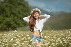 Beautiful young girl in chamomile field. Carefree happy brunette. Woman with healthy wavy hair having fun outdoor in nature. Daydreaming stock photography