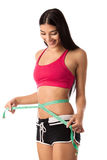 Beautiful young girl checking her waistline with a measuring tape Royalty Free Stock Photography