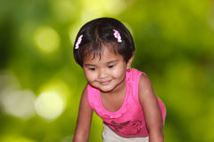 Beautiful young girl child happily playing in a park Stock Image