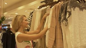 A beautiful young girl is choosing clothes in a store. Touches the clothes.
