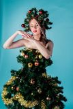 Beautiful young girl in a Christmas tree costume royalty free stock photo