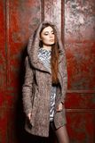 Beautiful young girl in a coat with hood near vintage wall Stock Image