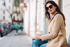 Beautiful and young girl in a coat and scarf and sunglasses sitting on the bench. Woman drinking coffee. Summer. Royalty Free Stock Photos