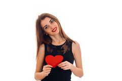 Beautiful young girl cocked her head in black dress smiles and keeps a postcard sweetheart Stock Image