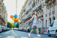 Beautiful young girl with colorful balloons running across the street in Paris Stock Images