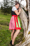 Beautiful young girl in a colourful dirndl. Beautiful young girl in a colourful traditional embroidered Bavarian dirndl standing leaning against a tree staring Stock Photography