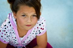 Beautiful young girl on a concrete patio. Royalty Free Stock Image