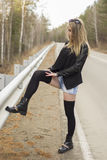 Beautiful young girl corrects stockings. Beautiful young girl corrects stockings leaning on the guardrail Royalty Free Stock Images