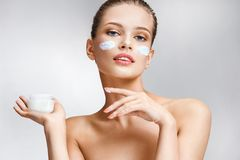 Beautiful young girl with cosmetic cream on her face. royalty free stock image