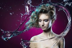 beautiful young girl covered with water splash on a violet background royalty free stock images