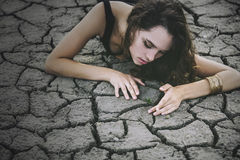 Beautiful young girl on the cracked earth in dress royalty free stock photography