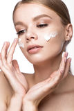 Beautiful young girl with cream on the skin, French manicure. Beauty face. royalty free stock images