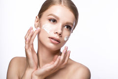 Beautiful young girl with cream on the skin, French manicure. Beauty face. Stock Image