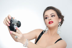 Beautiful young girl with creative make-up and hair style taking photos of herself with a camera. Fashionable attractive woman Royalty Free Stock Images