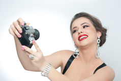 Beautiful young girl with creative make-up and hair style taking photos of herself with a camera. Fashionable attractive woman Royalty Free Stock Photography