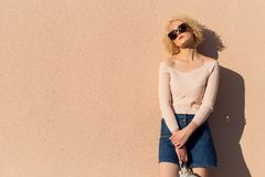 Beautiful  young girl with curls in sunglasses stands near the wall in sunlight at sunset Royalty Free Stock Images