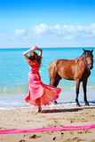 The beautiful young girl dances on coast. Nearby there is horse Royalty Free Stock Image