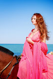 The beautiful young girl dances on coast. Nearby there is horse Stock Photo