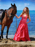 The beautiful young girl dances on coast. Nearby there is horse Stock Photos