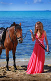 The beautiful young girl dances on coast. Nearby there is horse Stock Images