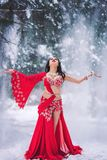 Beautiful young girl dancing belly dance in red dress in winter in a park on the snow. royalty free stock photography