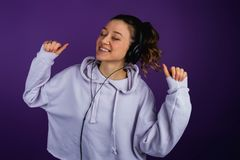 Beautiful young girl is dancing in headphones in a sweatshirt on a purple background.  Stock Image