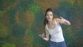 Beautiful young girl dancing. He listens to music on headphones. Very nice moves. stock video