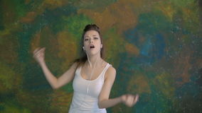 Beautiful young girl dancing. He listens to music on headphones. Very nice moves. stock footage