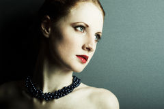 The beautiful young girl with a dark blue beads Stock Images