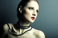 The beautiful young girl with a dark blue beads on a neck Stock Images