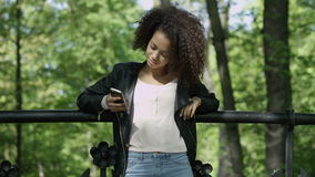 Beautiful young girl with dark curly hair using her cell phone, outdoor. Portrait of relaxed young lady in a summer park reading a text message on her mobile stock footage