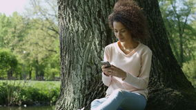 Beautiful young girl with dark curly hair using her cell phone, outdoor. Portrait of relaxed young lady in a summer park writing a text message on her mobile stock video