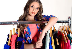 Beautiful young girl with dark curly hair in wardrobe room Royalty Free Stock Photos