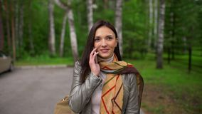 Beautiful young woman with attractive smile is speaking on her mobile phone, outdoors in summer. slow-motion stock video
