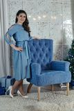 Beautiful young girl with dark hair stands near a blue armchair Royalty Free Stock Photography