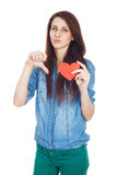 Beautiful young girl in denim blue shirt standing on a white background with a red paper heart in hands. Stock Photos