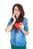Beautiful young girl in denim blue shirt standing on a white background with a red paper heart in hands. Royalty Free Stock Image