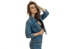 Beautiful young girl in denim clothes holding her hand near the hair and looks toward. Isolated on white background Royalty Free Stock Photography