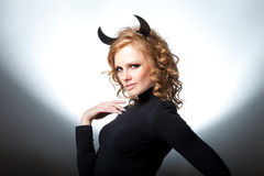 The beautiful young girl a devil. Glamour girl the blonde with horns Stock Photo