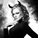 The beautiful young girl a devil. Glamour girl the blonde with horns Royalty Free Stock Image