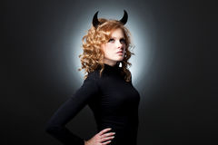 The beautiful young girl a devil. Glamour girl the blonde with horns Royalty Free Stock Photo